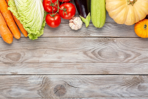 Geassorteerde rauwe biologische verse groenten op houten tafel. verse tuin vegetarisch eten. herfst seizoensgebonden beeld van boerentafel met pompoenen, aubergine, squash, knoflook, kool, tomaten. vrije ruimte.