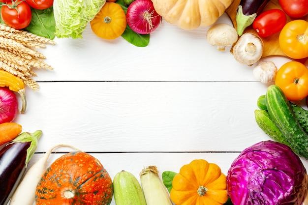 Geassorteerde rauwe biologische verse groenten op witte houten tafel. verse tuin vegetarisch eten. herfst seizoensgebonden beeld van boerentafel met champignons, rogge, komkommers, tomaten, aubergines, pompoenen.
