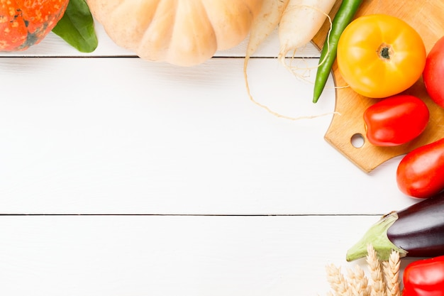 Geassorteerde rauwe biologische verse groenten op witte houten tafel.
