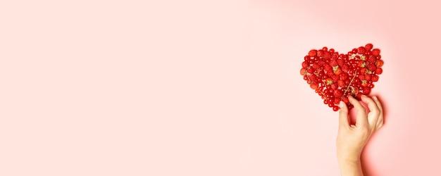 Geassorteerde rode bessen van frambozen, krenten en aardbeien, en een vrouwelijke hand neemt een bes