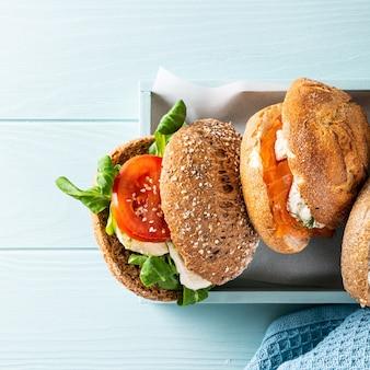 Geassorteerde sandwiches in houten kist op blauwe houten oppervlak. gezond voedselconcept met exemplaarruimte. bovenaanzicht