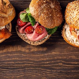 Geassorteerde sandwiches op houten oppervlak. gezond voedselconcept met exemplaarruimte. bovenaanzicht
