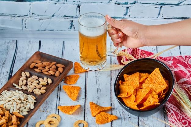 Geassorteerde snacks, chips en bier op blauwe tafel. tafel voor een groep vrienden.