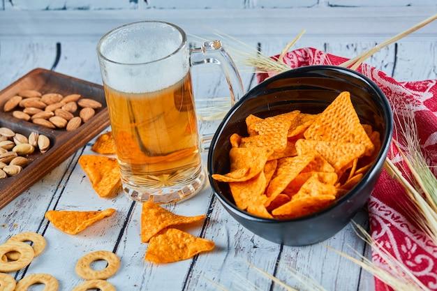Geassorteerde snacks, chips en een glas bier op blauwe tafel.