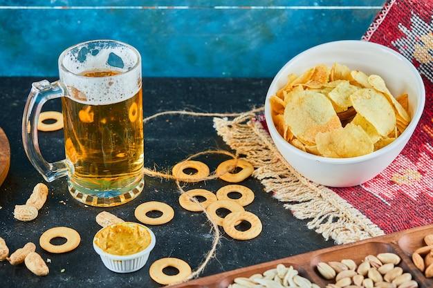 Geassorteerde snacks, chips en een glas bier op donkere tafel.