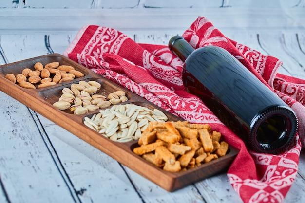 Geassorteerde snacks en een fles wijn op de blauwe tafel. crackers, zonnebloempitten, pistachenoten, amandelen.