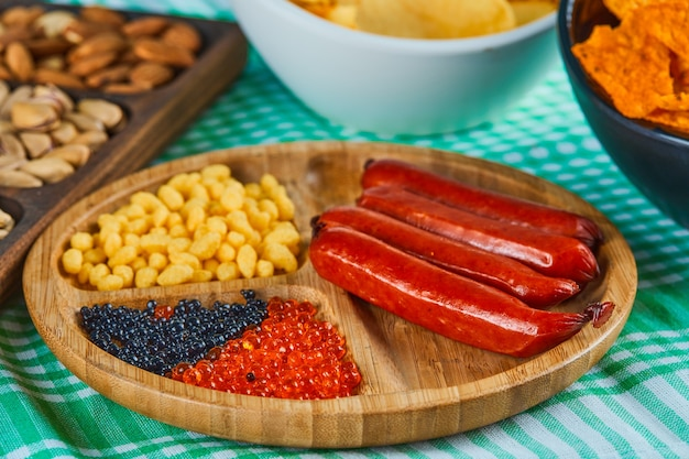 Geassorteerde snacks, kom chips en een bord worst op een blauwe tafel.