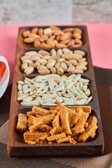 Geassorteerde snacks op de roze tafel. pistachenoten, zonnebloempitten, amandelen, crackers.