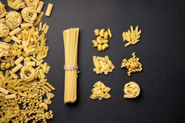 Geassorteerde soorten pasta op zwarte achtergrond exemplaarruimte voor ontwerp.