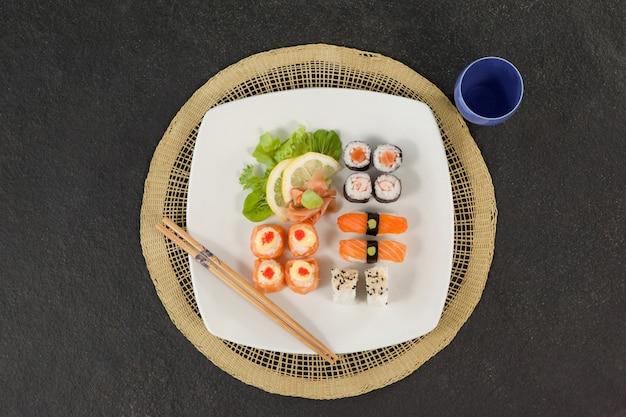 Geassorteerde sushi set geserveerd met stokjes en glas op sushi mat