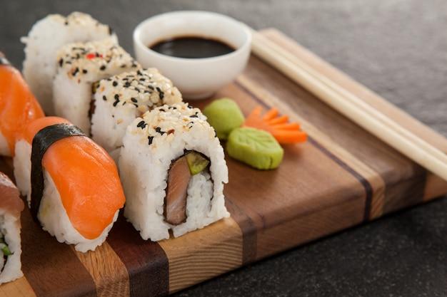Geassorteerde sushi set geserveerd met stokjes en sojasaus op een houten bord