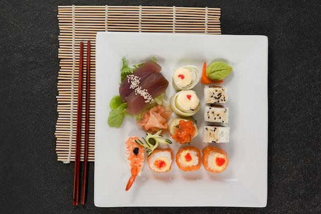 Geassorteerde sushi set geserveerd met stokjes in witte plaat op sushi mat