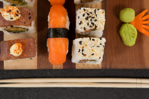 Geassorteerde sushi set geserveerd met stokjes op een houten bord