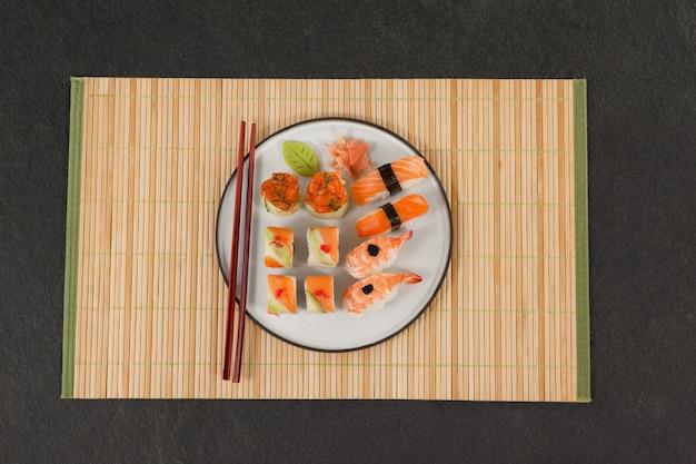 Geassorteerde sushi set geserveerd met stokjes op sushi mat