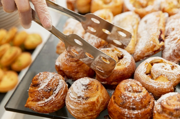Geassorteerde taarten op tafel. catering bij evenementen. een gehandschoende hand van een arbeider pakt een brood met een tang.