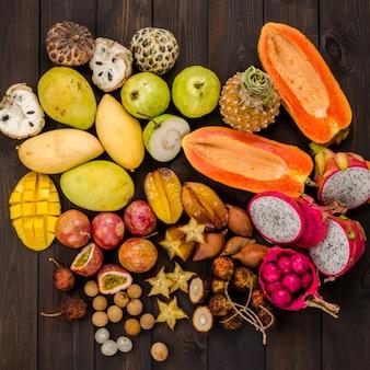 Geassorteerde thaise tropische vruchten op een donkere houten rustieke achtergrond.