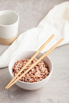 Geassorteerde veelkleurige wilde rijst in keramische kom en eetstokjes met drinkbeker water. zwarte, bruine en witte rijst.