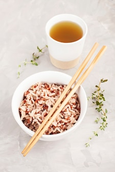 Geassorteerde veelkleurige wilde rijst in keramische kom en eetstokjes met groene thee. zwarte, bruine en witte rijst.