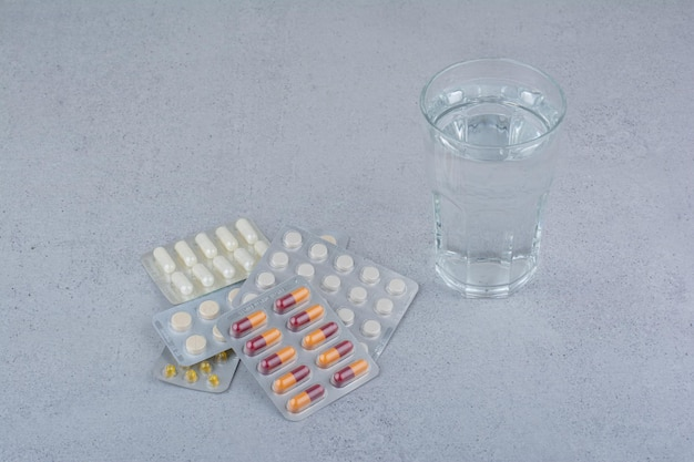 Geassorteerde verpakkingen van capsules en pillen met een glas water.