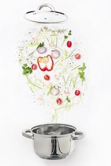 Geassorteerde verse groenten die in een kom vallen