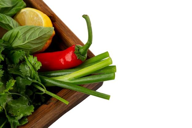 Geassorteerde verse kruiden op een houten dienblad. geserveerd met citroen en hete rode chili. vitaminen en gezonde voeding. icholated op een witte achtergrond. bovenaanzicht. ruimte voor tekst.