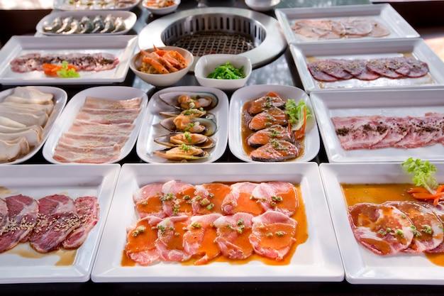 Geassorteerde vlees en zeevruchten ongekookt en koffiebrander klaar om te worden gegrild
