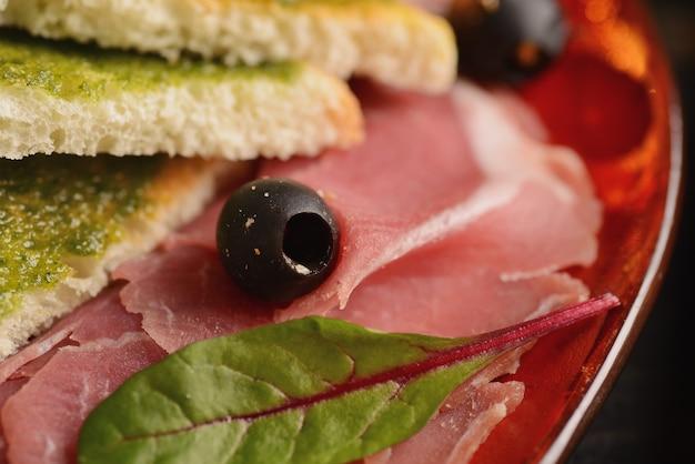 Geassorteerde worstjes, jamon en ham met plakjes gebakken brood op een rode plaat. op een houten tafel
