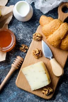 Geassorteerde zelfgemaakte stukjes kaas met honing, fruit, koekjes en noten op tafel. vers zuivelproduct, gezonde biologische voeding. heerlijk voorgerecht.