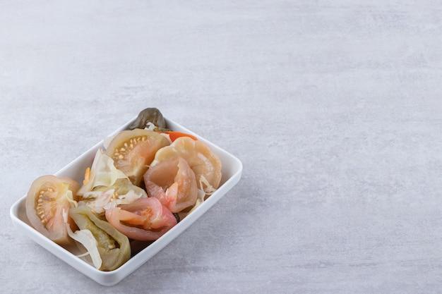 Geassorteerde zoute groenten in het zuur in het zuur die op een steenlijst worden geplaatst.
