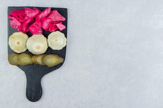Geassorteerde zoute groenten op zwart bord.