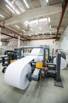 Geautomatiseerde drukpers met witte papierrol in industriële winkel