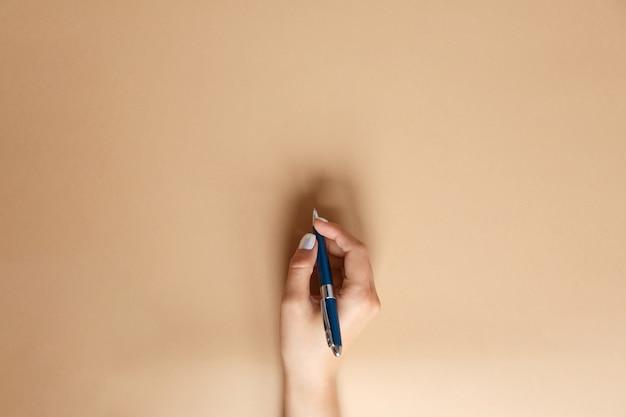 Gebaar en teken, vrouwelijke hand met metalen blauwe pen en schrijven op bruin, plat leggen