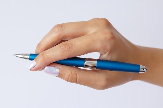 Gebaar en teken, vrouwelijke hand met metalen blauwe pen op wit