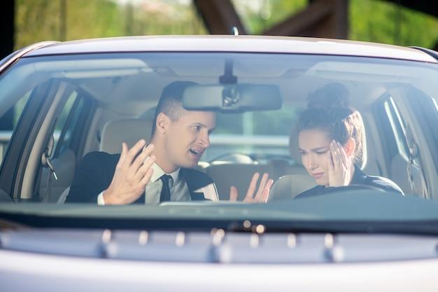 Gebaar ernstige man en ongelukkige vrouw in een auto
