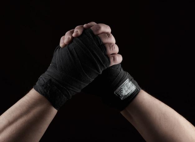 Gebaar van vriendschap, twee mannelijke handen van een atleet die met een zwart textielverband wordt gebonden