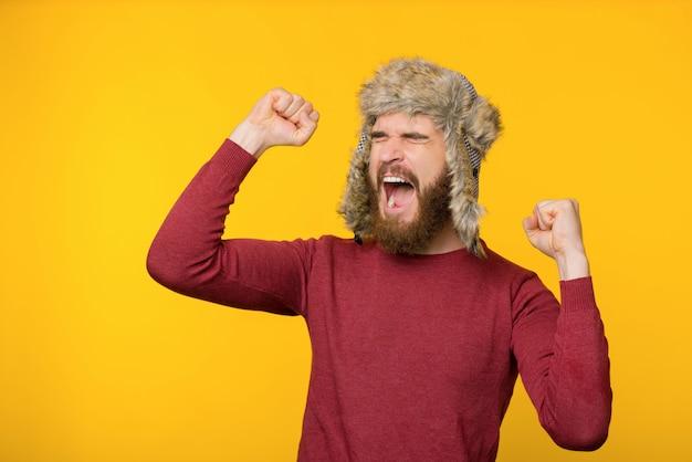 Gebaarde mens die een hoed van de comfortwinter dragen, vieren, gillend met gesloten omhoog ogen en wapens, geïsoleerde achtergrond