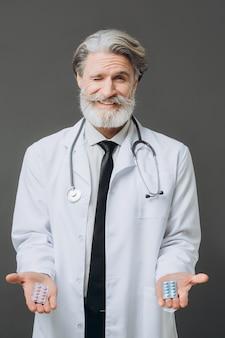 Gebaarde senor arts die pillen op grijze muur geeft