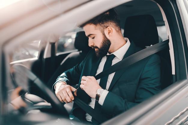 Gebaarde zakenman in formele slijtage vastmakende veiligheidsgordel in zijn auto.