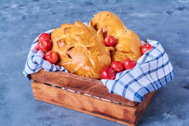 Gebak broodje met kersen op een houten bord op blauw