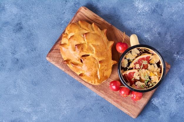 Gebak broodje met kruidenthee op een houten bord op blauw