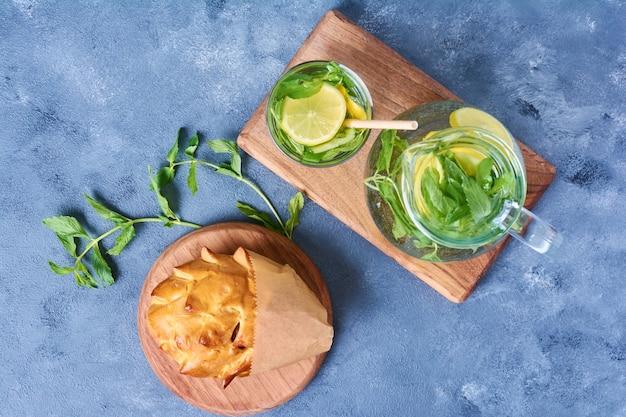 Gebak broodje met mochito op een houten bord op blauw