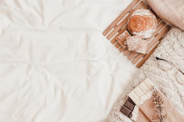 Gebak, chocolade met kruid en plaid die op witte bedsheet liggen