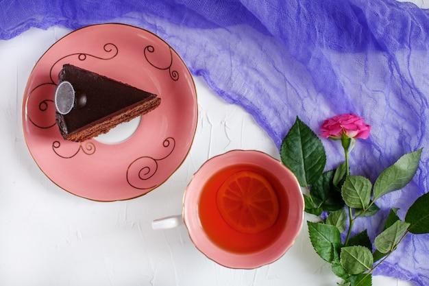 Gebak en hete thee op een dienblad op bilomuuachtergrond.