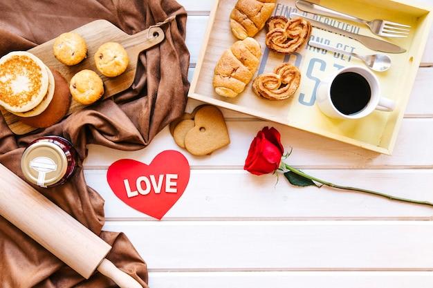 Gebak en koffie dichtbij hart en roos