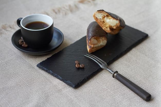 Gebak gevuld met room, traditionele franse eclairs met chocolade en kopje espresso.