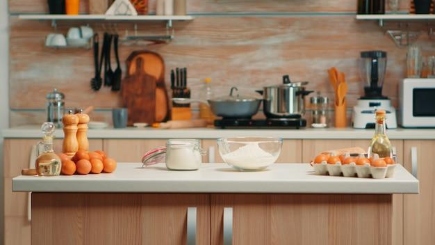 Gebak ingrediënten voor zelfgemaakte taarten en brood in lege keuken. moderne eetkamer uitgerust met keukengerei klaar om te koken met tarwemeel in glazen kom en verse eieren op tafel