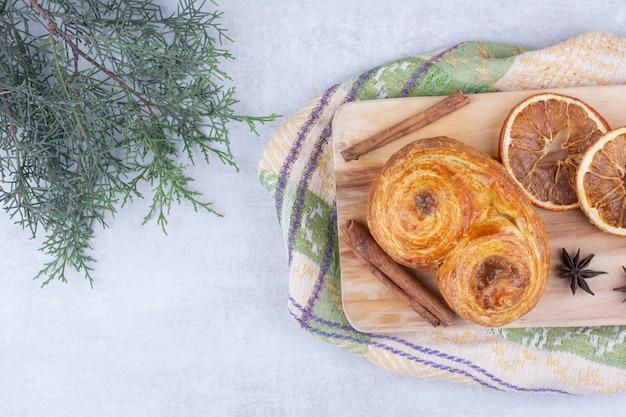 Gebak met kaneelstokjes, kruidnagel en sinaasappelen op een houten bord.