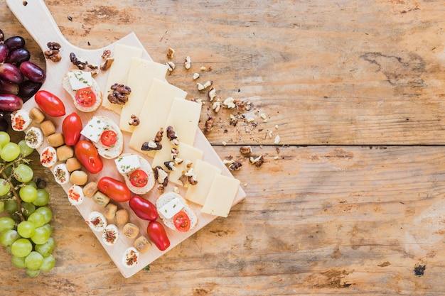 Gebak, sandwiches, tomaten, walnoten en kaasplakken op houten bureau