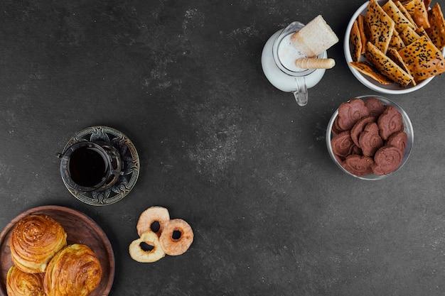 Gebakbroodjes en crackers met een glas thee en melk op zwart, bovenaanzicht.