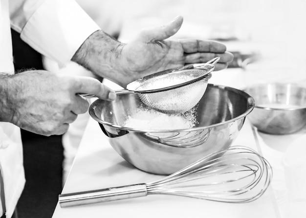 Gebakchef-kok baker die bloem zeven in een kom in de keuken van de bakkerij